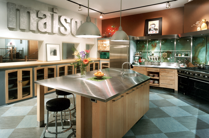 stainless-steel-counter-and-tabletop-custom-maple-cabinetry-along-wall-and-beneath-counters-and-table