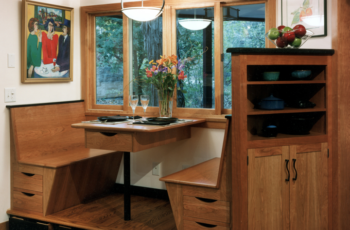cozy-breakfast-nook-with-windows-to-porch-custom-shelving-behind-benches-drawers-beneath-benches